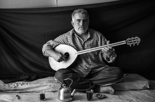 "Omar, 37, holds a buzuq, or long-necked lute – the most important thing that he was able to bring with him to Domiz refugee camp in the Kurdistan Region of Iraq. Omar decided it was time to flee his home in the Syrian capital of Damascus the night that his neighbours were killed. ""The killers came into their home, whoever they were, and savagely cut my neighbour and his two sons,"" he recalls. Omar says that playing the buzuq ""fills me with a sense of nostalgia and reminds me of my homeland. For a short time, it gives me some relief from my sorrows."