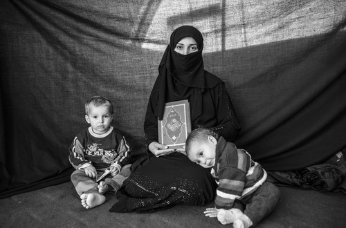 "Iman, 25, with her son Ahmed and daughter Aishia, in Nizip refugee camp, Turkey. They fled their home in Aleppo after months of conflict. Iman decided it was time to flee when she heard accounts of sexual harassment against women in Aleppo. The journey to Turkey was full of danger – Iman lost five relatives. The most important thing she was able to bring with her is the Koran she holds in this photograph. She says the Koran inspires a sense of protection. ""As long as I have it with me, I'm connected to God."""