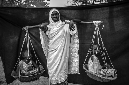 Several months before this picture was taken, repeated bombing raids forced Dowla, 22, and her six children to flee their village in Sudan's Blue Nile state. The most important object she was able to bring with her is the wooden pole balanced over her shoulder, with which she carried her six children during the 10-day journey from Gabanit to South Sudan. At times, the children were too tired to walk, forcing her to carry two on either side. Doro refugee camp, Maban County, South Sudan.